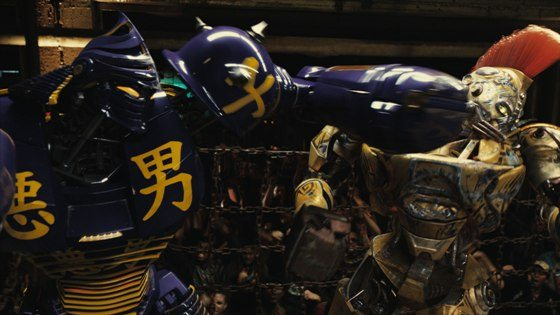 Noisy Boy lands a hard punch to the steel face of Midas in a boxing match between the two robots at the Crash Palace in a scene from REAL STEEL.
