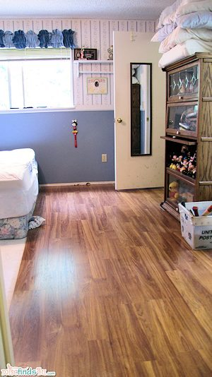 Master Bedroom Floor Replacement - left site painted, right side new Pergo flooring