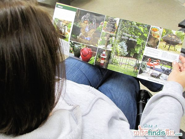 Judy uses the Kmart Circular Catalog to read up on the products