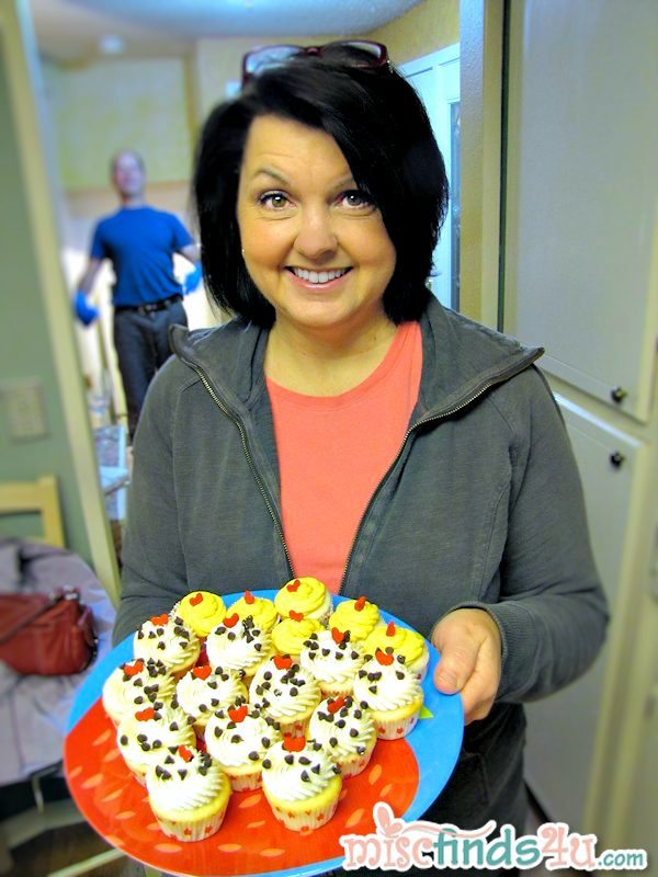 My sister Judy with one of 2 plates of amazing cupcakes - photobomber is my husband ;) #keurigparty