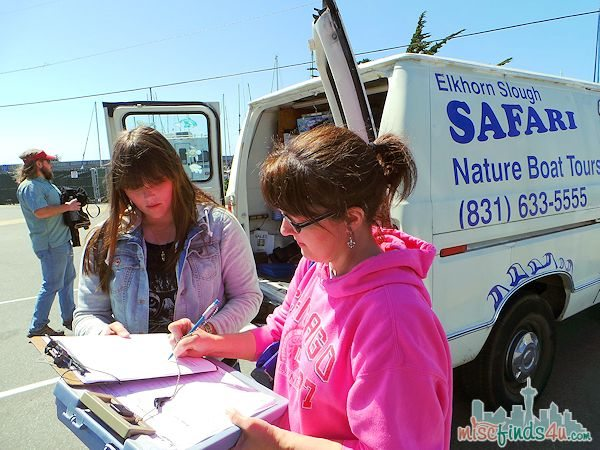 Check-in for the Elkhorn Slough Safari Guided Nature Boat Tour is at a white van with the logo on the side in the Moss Landing Marina parking lot. You will be asked to sign a waiver and then wait at the door to the dock to be boarded as a group.