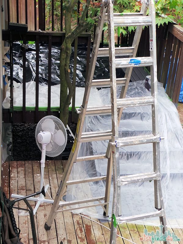 The perils of painting a deck in Seattle - fans to help dry it and plastic to keep rain for descending on it.