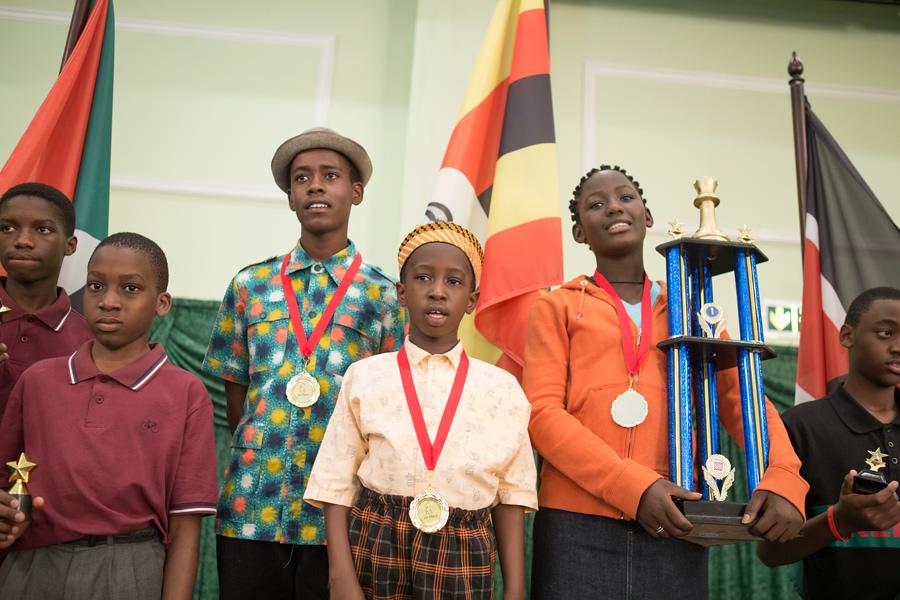 Madina Nalwanga (holding trophy) as Phiona Mutesi